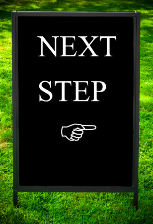 the next step: NEXT STEP message and hand pointing to the right on sidewalk blackboard sign against green grass background. Copy Space available. Concept image