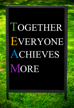 achieves: TOGETHER EVERYONE ACHIEVES MORE  message on sidewalk blackboard sign against green grass background. Copy Space available. Concept image