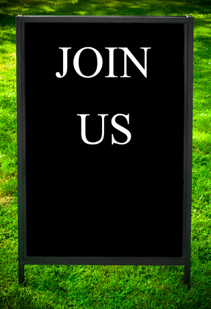 advertise with us: JOIN US  message on sidewalk blackboard sign against green grass background. Copy Space available. Concept image