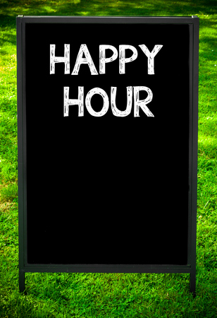 hour: HAPPY HOUR  message on sidewalk blackboard sign against green grass background. Copy Space available. Concept image Stock Photo