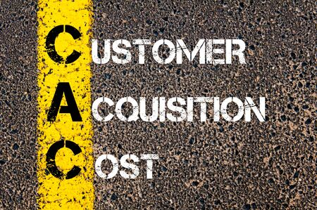 acquisition: Business Acronym CAC as CUSTOMER ACQUISITION COST. Yellow paint line on the road against asphalt background. Conceptual image