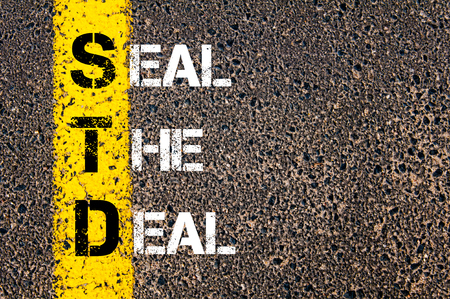 std: Business Acronym STD as SEAL THE DEAL. Yellow paint line on the road against asphalt background. Conceptual image