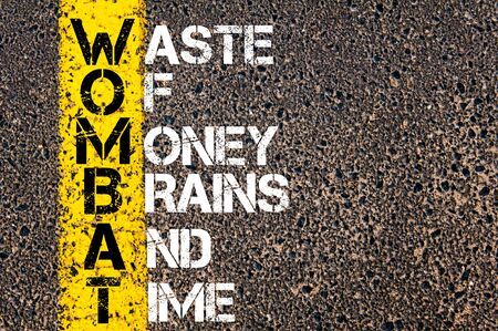 corporate waste: Business Acronym WOMBAT as WASTE OF MONEY, BRAINS AND TIME. Yellow paint line on the road against asphalt background. Conceptual image Stock Photo