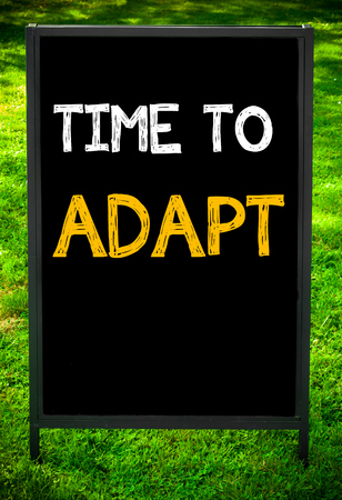 available time: TIME TO ADAPT  message on sidewalk blackboard sign against green grass background. Copy Space available. Concept image Stock Photo