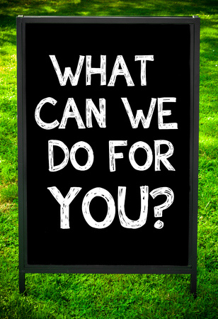 WHAT CAN WE DO FOR YOU?  message on sidewalk blackboard sign against green grass background. Copy Space available. Concept image