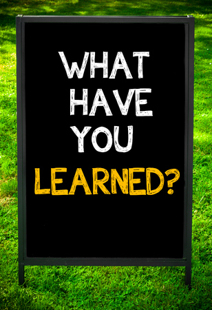 learned: WHAT HAVE YOU LEARNED?  message on sidewalk blackboard sign against green grass background. Copy Space available. Concept image Stock Photo