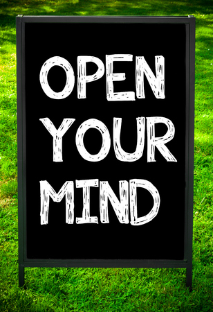 open mind: OPEN YOUR MIND  message on sidewalk blackboard sign against green grass background. Copy Space available. Concept image