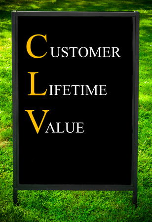 lifetime: Business Acronym CLV as CUSTOMER LIFETIME VALUE. Message on sidewalk blackboard sign against green grass background. Concept image