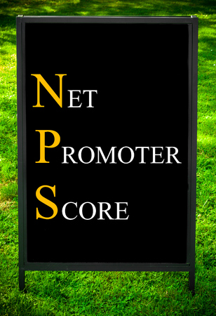promoter: Business Acronym NPS as NET PROMOTER SCORE. Message on sidewalk blackboard sign against green grass background. Concept image
