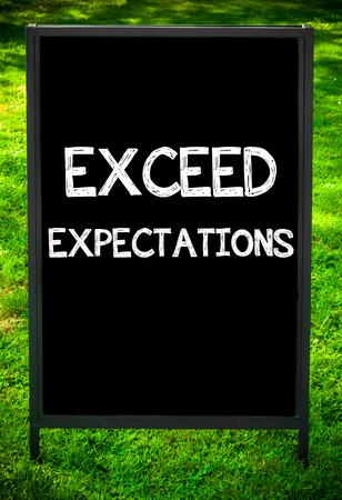 expectations: EXCEED EXPECTATIONS  message on sidewalk blackboard sign against green grass background. Copy Space available. Concept image