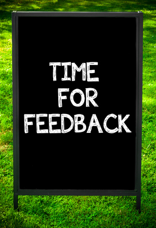 available time: TIME FOR FEEDBACK  message on sidewalk blackboard sign against green grass background. Copy Space available. Concept image