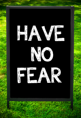 no fear: HAVE NO FEAR  message on sidewalk blackboard sign against green grass background. Copy Space available. Concept image
