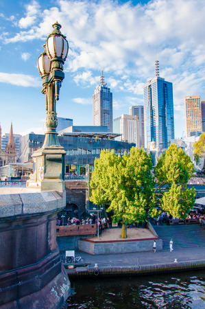 flinders: Melbourne, Australia - February 20, 2015: View over Yarra River and City Skyscrapers from Princes Bridge.It has been ranked the worlds most livable city since 2011, often referred to as Australias cultural capital.