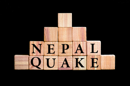 quake: WordS NEPAL QUAKE. Wooden small cubes with letters isolated on black background with copy space available. Concept image. Stock Photo
