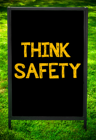 think safety: THINK SAFETY  message on sidewalk blackboard sign against green grass background. Copy Space available. Concept image Stock Photo