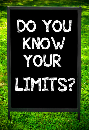 limits: DO YOU KNOW YOUR LIMITS?  message on sidewalk blackboard sign against green grass background. Copy Space available. Concept image