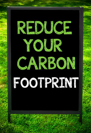 green footprint: REDUCE YOUR CARBON FOOTPRINT  message on sidewalk blackboard sign against green grass background. Copy Space available. Concept image