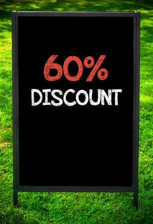 sixty: SIXTY PERCENT DISCOUNT  message on sidewalk blackboard sign against green grass background. Copy Space available. Concept image