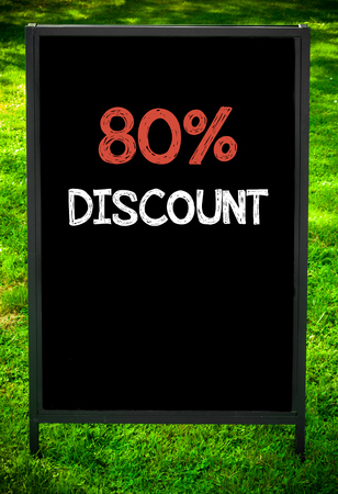 eighty: EIGHTY PERCENT DISCOUNT  message on sidewalk blackboard sign against green grass background. Copy Space available. Concept image Stock Photo