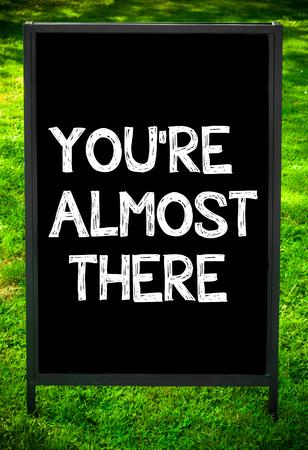 Je bent er bijna bericht op de stoep bordteken tegen het groene gras achtergrond. Kopieer beschikbare ruimte. Concept beeld