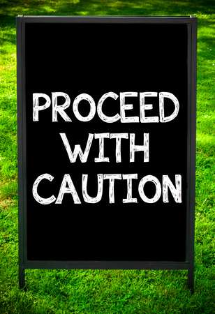 to proceed: PROCEED WITH CAUTION  message on sidewalk blackboard sign against green grass background. Copy Space available. Concept image