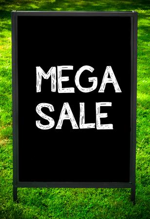 sidewalk sale: MEGA SALE  message on sidewalk blackboard sign against green grass background. Copy Space available. Concept image