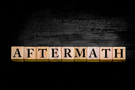 aftermath: Word AFTERMATH. Wooden small cubes with letters isolated on black background with copy space available. Concept image.