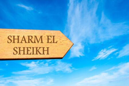 sharm: Wooden arrow sign pointing destination SHARM EL SHEIKH against clear blue sky with copy space available. Travel destination conceptual image