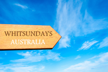 whitsundays: Wooden arrow sign pointing destination WHITSUNDAYS AUSTRALIA against clear blue sky with copy space available. Travel destination conceptual image Stock Photo