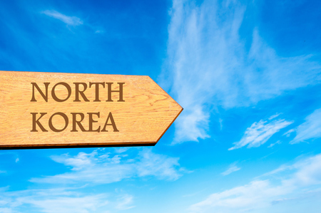 north arrow: Wooden arrow sign pointing destination NORTH KOREA against clear blue sky with copy space available. Travel destination conceptual image Stock Photo