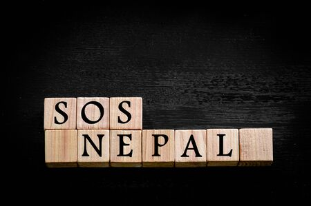 Message SOS NEPAL. Wooden small cubes with letters isolated on black background with copy space available. Concept image. Фото со стока - 39582833