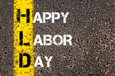 first day: Acronym HLD as HAPPY LABOR DAY. Yellow paint line on the road against asphalt background. Conceptual image Stock Photo