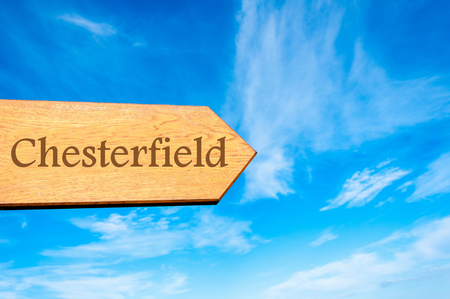 chesterfield: Wooden arrow sign pointing destination CHESTERFIELD, ENGLAND against clear blue sky with copy space available Stock Photo
