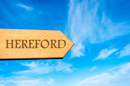 hereford: Wooden arrow sign pointing destination HEREFORD, ENGLAND against clear blue sky with copy space available.