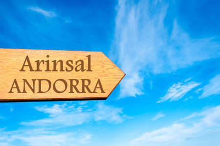 tourism in andorra: Wooden arrow sign pointing destination ARINSAL, ANDORRA against clear blue sky with copy space available. Stock Photo