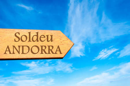 tourism in andorra: Wooden arrow sign pointing destination SOLDEU, ANDORRA against clear blue sky with copy space available. Stock Photo