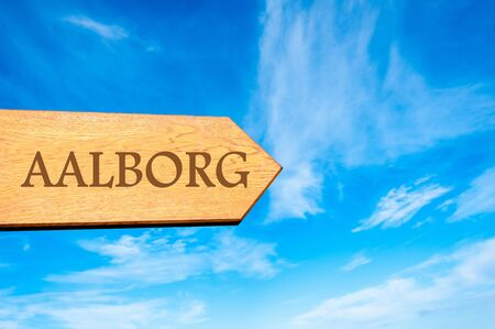 Wooden arrow sign pointing destination AALBORG, DENMARK against clear blue sky with copy space available