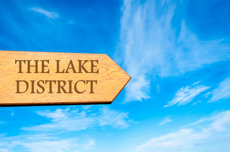 lake district england: Wooden arrow sign pointing destination THE LAKE DISTRICT, ENGLAND against clear blue sky with copy space available