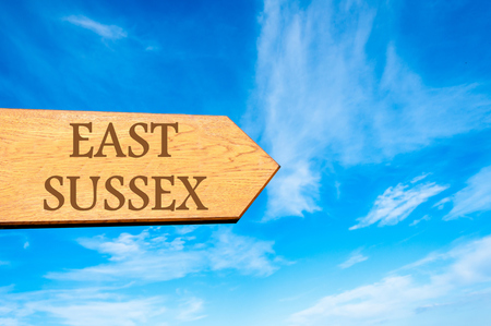 sussex: Wooden arrow sign pointing destination EAST SUSSEX, ENGLAND against clear blue sky with copy space available Stock Photo
