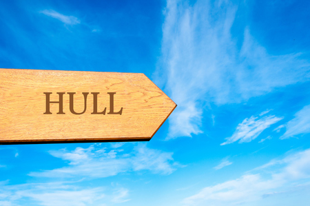 hull: Wooden arrow sign pointing destination HULL, ENGLAND against clear blue sky with copy space available