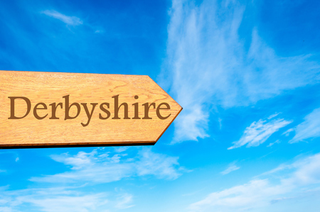 derbyshire: Wooden arrow sign pointing destination DERBYSHIRE, ENGLAND against clear blue sky with copy space available
