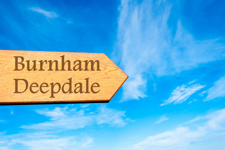 burnham: Wooden arrow sign pointing destination Burnham Deepdale, ENGLAND against clear blue sky with copy space available Stock Photo