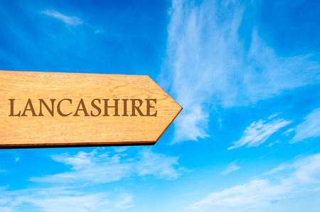 lancashire: Wooden arrow sign pointing destination LANCASHIRE, ENGLAND against clear blue sky with copy space available