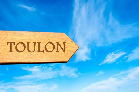 toulon: Wooden arrow sign pointing destination TOULON FRANCE against clear blue sky with copy space available Stock Photo