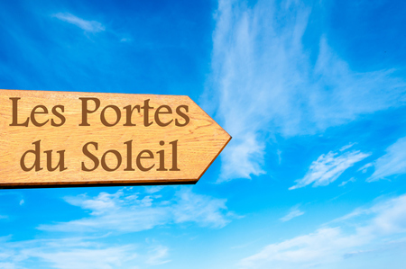 soleil: Wooden arrow sign pointing destination Les Portes du Soleil FRANCE against clear blue sky with copy space available Stock Photo