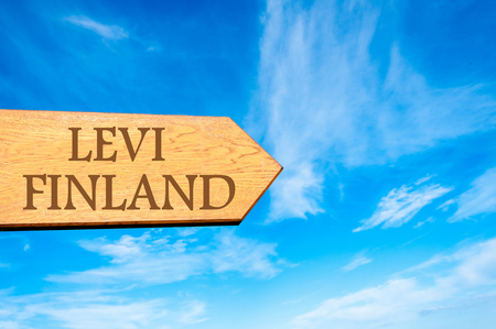 levi: Wooden arrow sign pointing destination LEVI, FINLAND against clear blue sky with copy space available