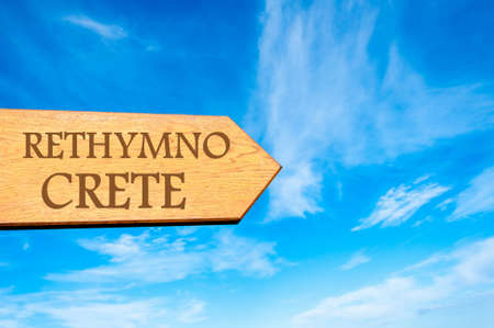 rethymno: Wooden arrow sign pointing destination RETHYMNO, CRETE, GREECE against clear blue sky with copy space available