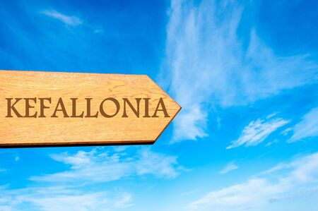 kefallonia: Wooden arrow sign pointing destination KEFALLONIA, GREECE against clear blue sky with copy space available Stock Photo