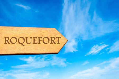 roquefort: Wooden arrow sign pointing destination ROQUEFORT, FRANCE against clear blue sky with copy space available