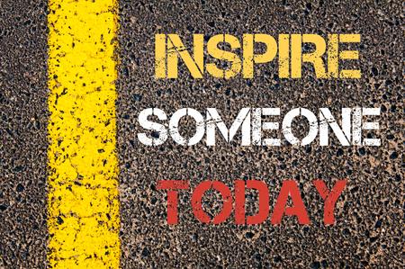 inspiracion: INSPIRE ALGUIEN HOY cita de motivaci�n. L�nea de pintura amarilla en el camino contra el fondo de asfalto Foto de archivo
